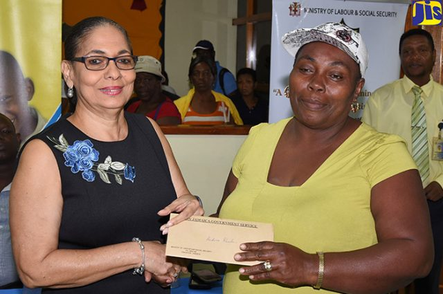 Minister of Labour and Social Security, Hon. Shahine Robinson (left), presents Portland resident, Andrea Rhoden, with an emergency relief cheque, at the Ministry's parish office, in Port Antonio, on February 2. Approximately 112 persons in Portland, who suffered losses during heavy rains in January, are selected to receive grants.